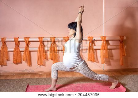 Healthy Maternity Lifestyle Concept. 40 Week Pregnant Middle Aged Caucasian Woman Doing Yoga Exercis