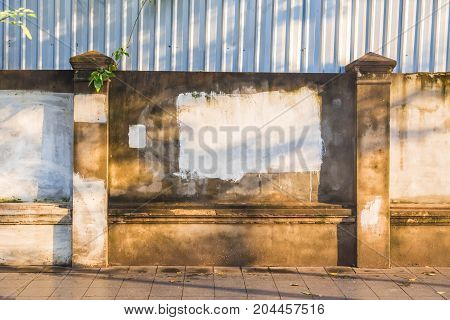 old weathered rustic concrete wall and fence along sidewalk with rough white paint in front of metal sheet construction fence