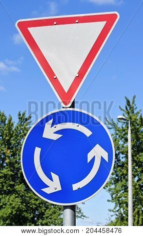 Yield and roundabout traffic signs on the road