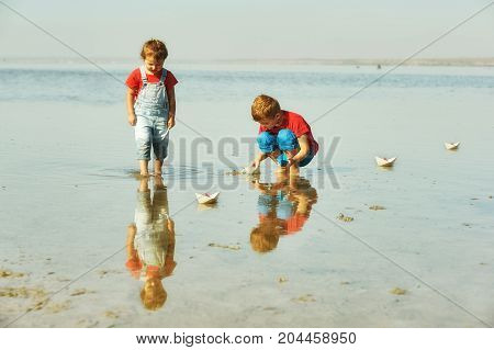 Cheerful children playing with paper boats . Brother and sister playing at the lake