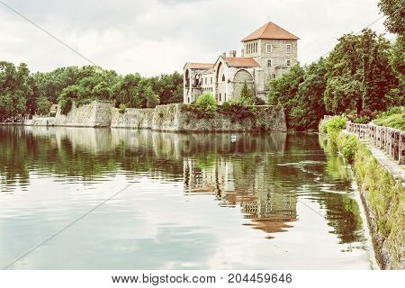 Beautiful castle in Tata Hungary. Travel destination. Architectural theme. Fortress is reflected in the lake. Photo filter.