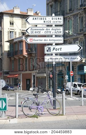 Nice, France - October 2012: Urban scnerey with traffic signs and people on the street in Nice, France in October 2012