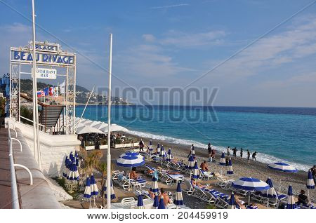 Nice, France - October 2012: People enjoying the autumn sun on beach of Nice, France in October 2012