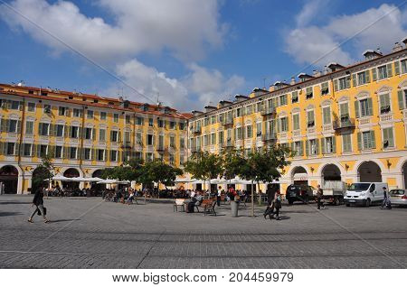 Nice, France - October 2012: Yellow buildings on public square in Nice, France, with people corssing the square, in 2012