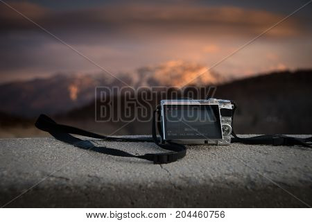 Small pockect size digital mirrorless camera photographing sunset over mountains