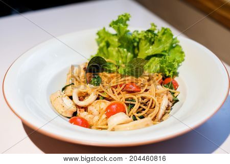 The spaghetti spicy seafood (squid shrimp) with basil tomato black pepper lettuce and paprika on white dish set on table for food background or texture - homemade food concept.
