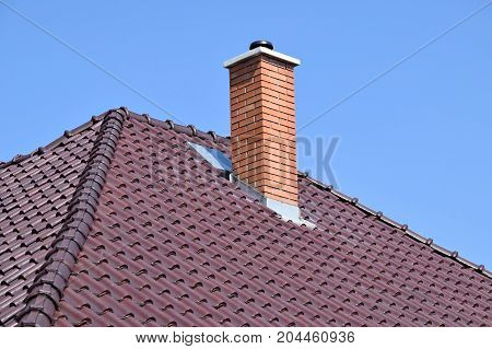 House roof with smoke stack against sky