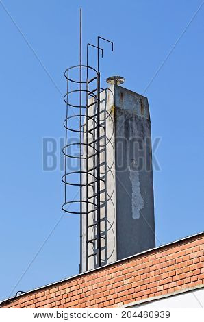 High smoke stack with ladder on the top of a building
