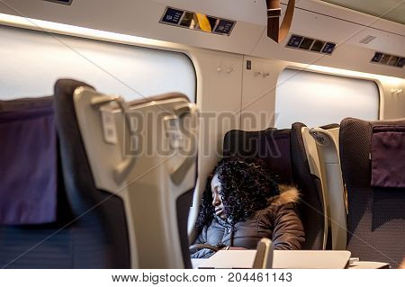 Rome Italy - October 30 2012: Young beautiful woman sleeping sitting in the train ride from Venice to Rome.