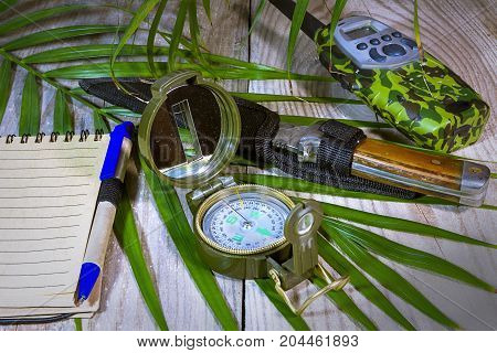 Compass lying on wooden boards, surrounded by tropical ferns, knife, walkie-talkie, notebook