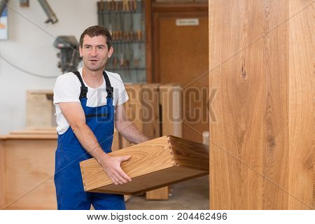 worker in blue dungarees in a carpenter's workshop