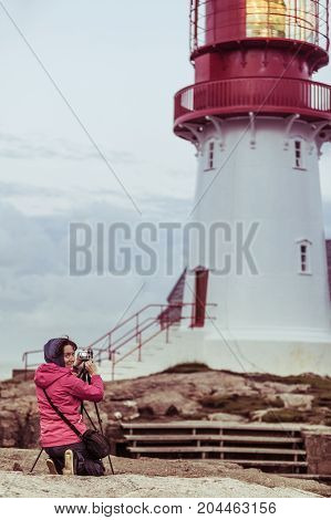 Female tourist traveler taking photo at historic red white lighthouse on the edge of rocky sea coast South Norway Lindesnes Fyr beacon