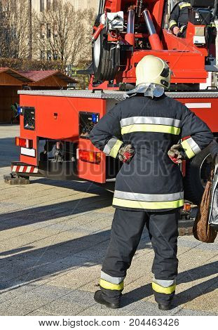 Firefighter stands next to a crane in the city