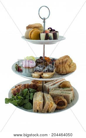 Assortment of high tea delicacies including sandwiches, scones, pies, sweet desserts isolated