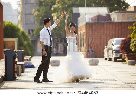 young asian bride and groom in wedding dress dancing in parking lot.