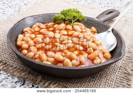 warm baked beans in tomato sauce served in a cast iron pan with parsley