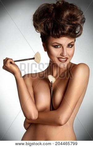 Cute adult brunette smiling at camera with brushes in studio