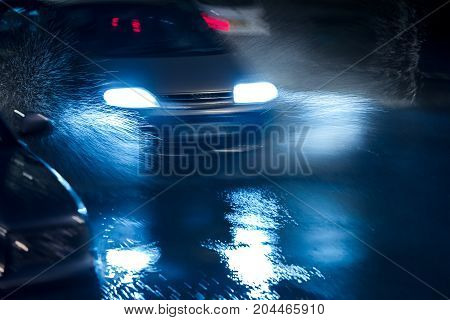 Cars Driving And Headlights Reflecting In Water Puddles