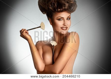 Portrait of sexy brunette with brushes smiling on camera in studio