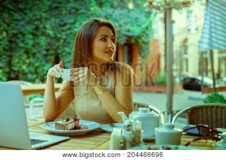 Cutie woman with cup of tea looking away in restaurant outdoors