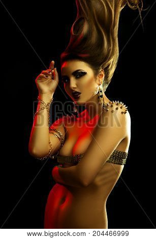 High contrast portrait of sexual woman with high creative hairstyle and golden accessories in studio