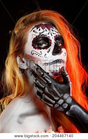 Readhead girl. Unreal couple, isolated. All souls day. Boy and girl in costumes of skeletons and sugar skull makeup.