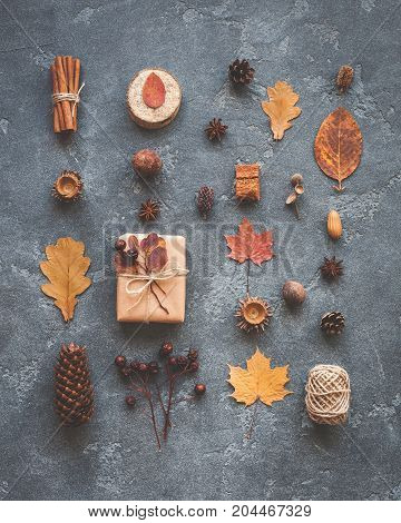 Autumn composition. Gift autumn leaves cinnamon sticks anise stars pine cones on black background. Flat lay top view