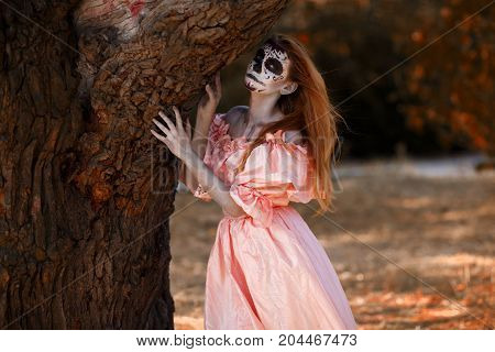 Full-length of readhead God of death outside in autumn park. Crazy make-up.