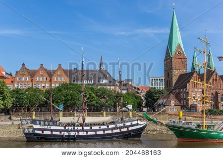 BREMEN, GERMANY - AUGUST 23, 2017: Historical ships and church along the river Weser in Bremen Germany