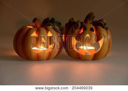Two Halloween pumpkins head jack lantern with burning candles