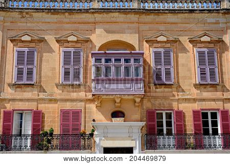 Traditional Maltese building with lilac coloured shutters in the old town Mdina Malta Europe.
