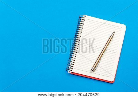 Notepad with pen on the blue background. Top view.