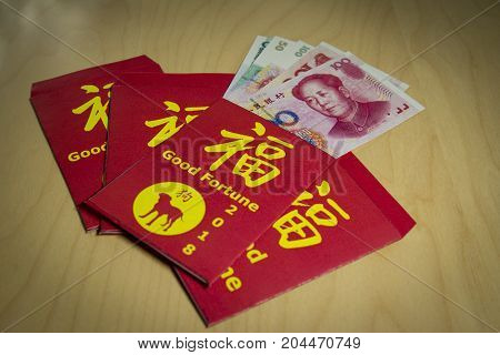 The red envelope or hong bao is used for giving money during Chinese New Year in China and Taiwan.2018 is the dog's year. Chinese words meaning Good fortune a dog's silhouette on it and yuan bills.