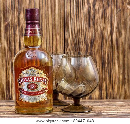 Ternopil Ukraine - August 26 2017: Bottle of Blended scotch whisky Chivas Regal. 12 years old scotch whiskey. Made in Scotland. Bottle of whisky with glass on wooden background.