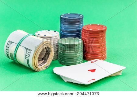 Poker chips deck of cards and money on green background.