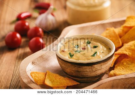 Mexican cheese dip served with nachos .