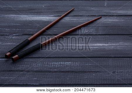 Brown Chopsticks on a wood black background