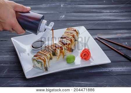 Bottle pouring sauce onto sushi. Squeeze bottle in man's hand. Japan sends greetings. Uramaki rolls from sushi cafe on white plate over black wooden background.