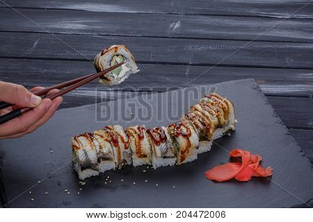 Sushi - Roll on a black plate with man hand holding in chopsticks one roll over black background