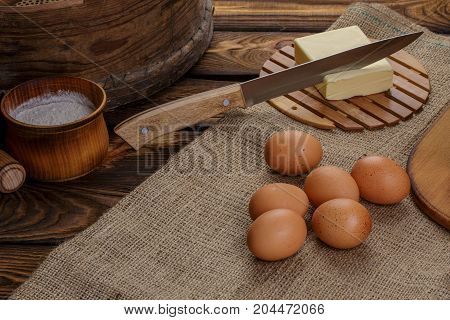 Ingredients for homemade bread over burlap and wooden broun background knife in butter