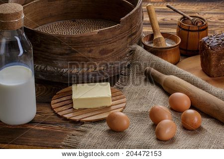 Organic products: eggs milk bread butter wheat on a wooden background and burlap