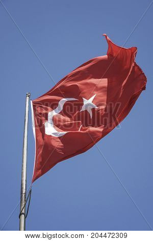 Turkish flag is waving against blue sky