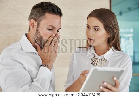 Two Coworkers Working On Tablet In Office Together