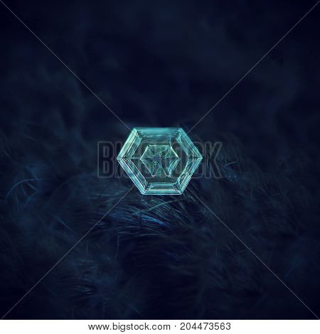Real snowflake at high magnification. Macro photo of simple hexagonal plate snow crystal with glowing inner pattern. Snowflake glittering on dark blue woolen background in natural light.