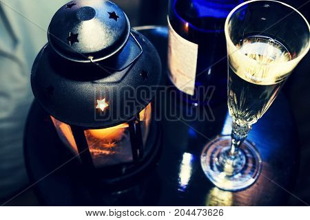 New Year Christmas. Champagne in glasses and in a bottle, a Christmas lantern with a burning candle on the festive table. winter holiday