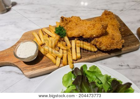 fish and chips with tartar sauce serve on the wooden board