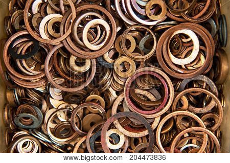 Many copper sealing washers of high pressure in plastic utensils. Copper washers of different sizes