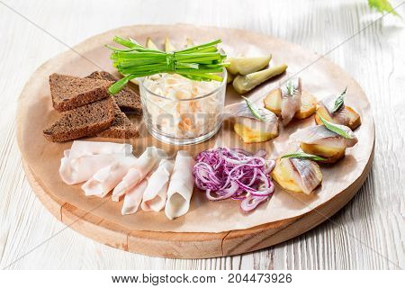 Sandwiches of potato slices with herring, red onions, herbs and rye bread. bacon slices and pickles. on wooden plate