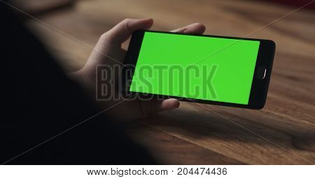 female teen girl hold smartphone with green screen over wood table, wide photo