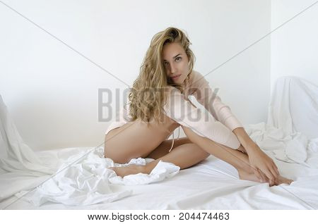 Health, sensuality, people and beauty concept - beautiful young girl sits in bed in white sheets, her hands resting on the legs